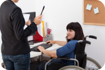 woman on a wheelchair working in a computer
