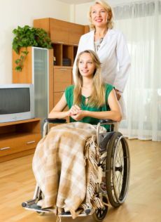 Happy doctor visiting handicapped young girl at home