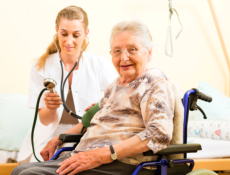 aged woman checked by her expert caretaker